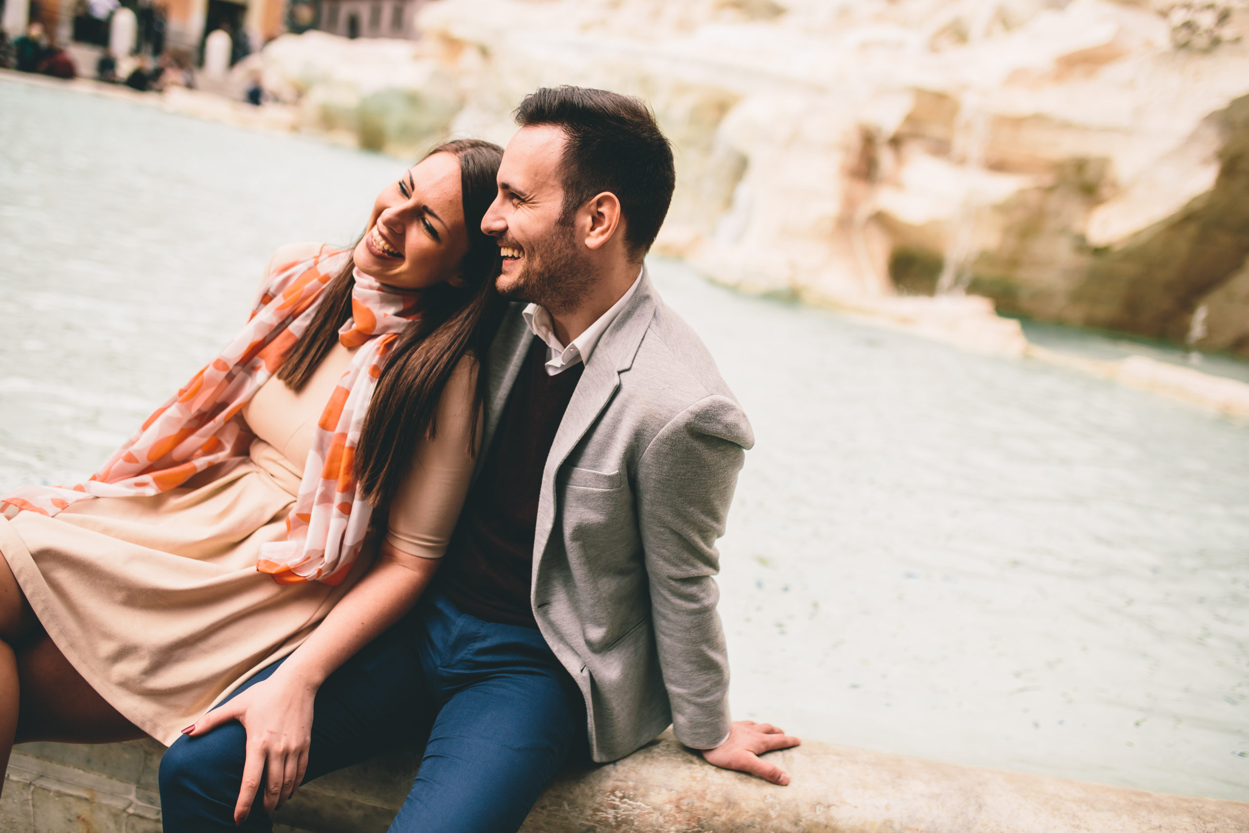 A happy woman and man sitting by a river, enjoying each other's company.